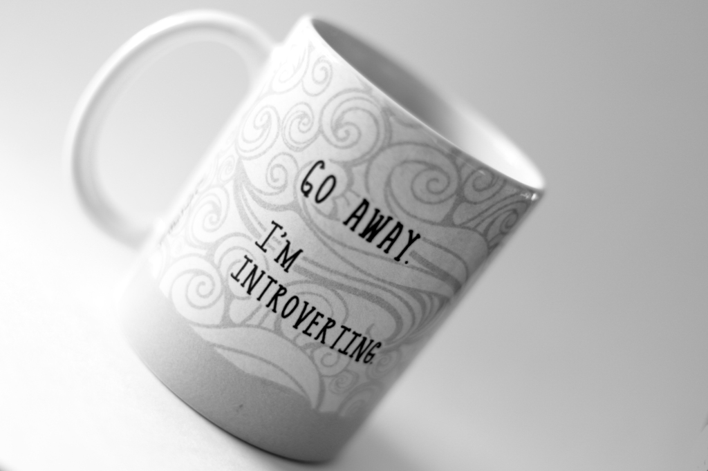 """Black and white image of a tilted mug that says """"GO AWAY. I'M INTROVERTING."""" in block letters against an abstract swirly design."""